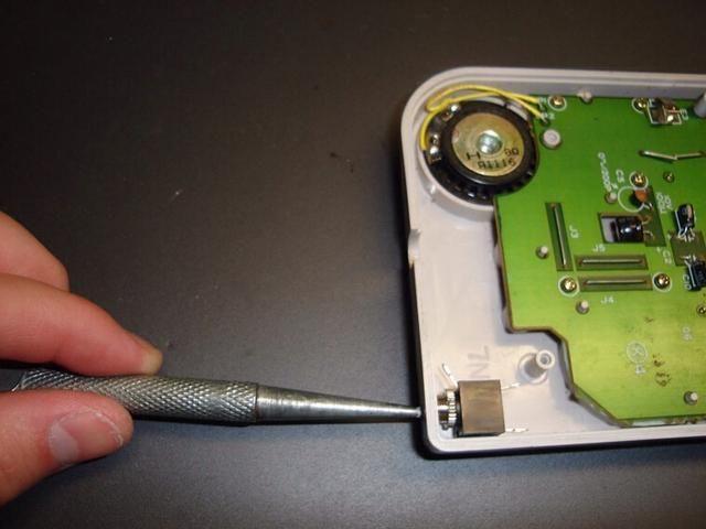 Ahora usa un punzón o rotulador para marcar el lugar donde se va a perforar el agujero. Pulse en el centro de la toma, saber donde se inserta el cable, hasta que tenga una marca visible en el plástico.